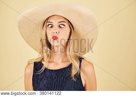 Portrait Of Funny Young Woman In Straw Hat Looking At Tip Of Her Nose