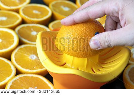 Freshly Squeezed Orange Juice. Preparing An Orange Fresh. Close-up Of The Hand Who Is Preparing An S