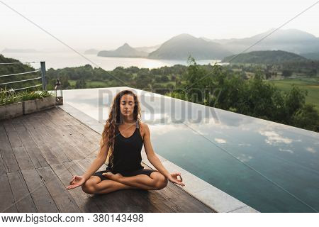 Woman Practicing Yoga In Lotus Position On Infinity Poolside With Beautiful Ocean And Mountain View