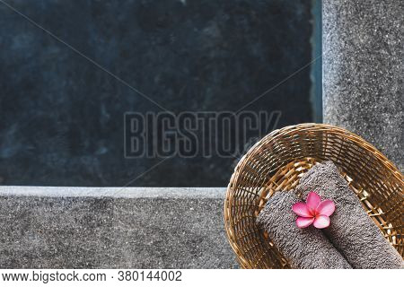 Two Gray Hand Towels In Wicker Basket On Poolside In Hotel Spa. Pink Frangipani Flower As Decoration