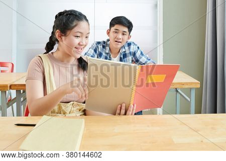 Smiling Vietnamese Schoolgirl Showing Test Answers In Copybook To Her Friend