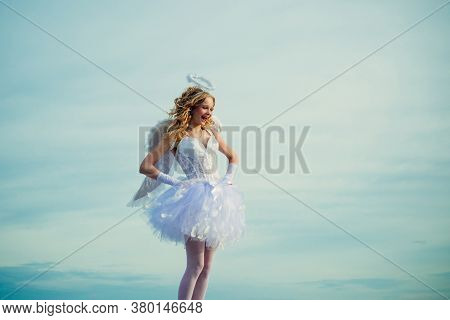 Charming Curly Little Girl In White Dress And Wings - Angel Cupid Girl. Enjoying Magic Moment. Prett