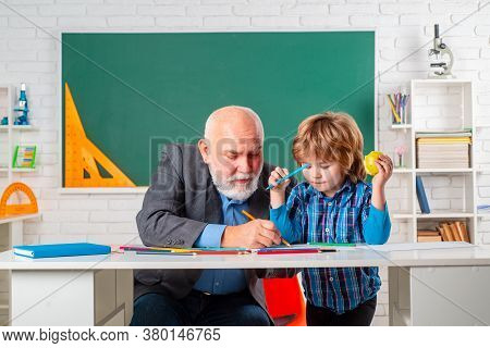 Professor And Pupil In Classroom At The Elementary School. Child At School Lesson With Senior Teache