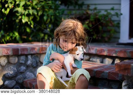 Child Lovingly Embraces His Pet Dog. Portrait Of A Little Cute Boy Kid With Doggy Relaxing On Nature