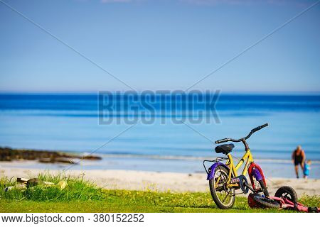 Gimsoya, Norway - July 17, 2018: Child Bikes With Safety Helmet Parked On Beach Seashore In Summer.