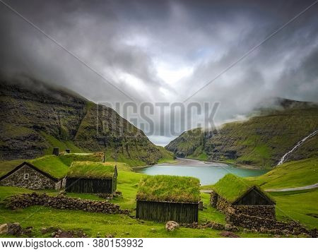 Small Houses Near A Blue Lake, A Small House Made Of Stones With Covered Grass On The Shore Of A Bea
