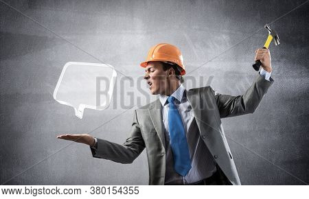 Furious Businessman Going To Crash Glass Speech Bubble With Hammer. Young Handsome Man In Business S