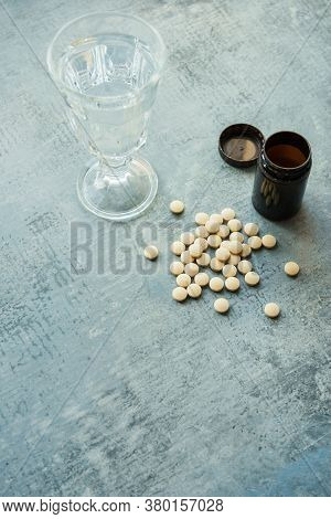 Yellow Round Tablets Or Pills Vitamins On Blue Stone Concrete Table With Black Plastic Bottle And Gl