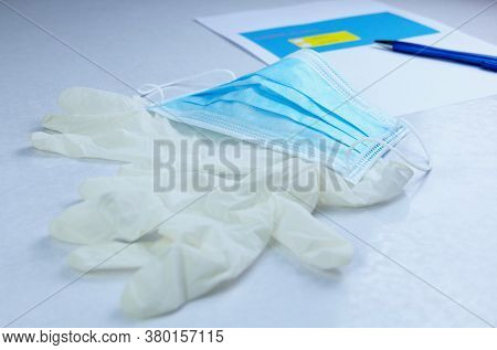 Mask And Medical Gloves On Table With Blurred Paperwork And Pen