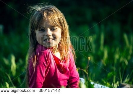Portrait of a smiling little cute girl lying on green green grass.