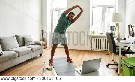 Personal Trainer. Full Length Shot Of Male Fitness Instructor Stretching His Body While Streaming, B