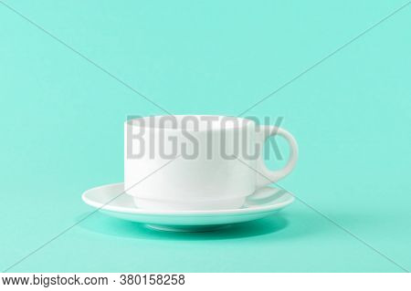Empty Porcelain Coffee Cup And A Saucer Over A Mint Green Color Background. White Ceramic Teacup. Mo
