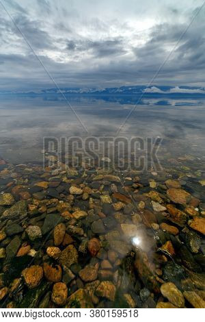 Lake Baikal In Summer Before A Thunderstorm With Colorful Stones Under Transparent Water, Vertical P