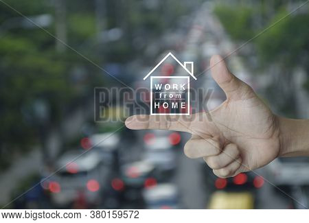 Work From Home Flat Icon On Finger Over Blur Of Rush Hour With Cars And Road In City, Business Socia