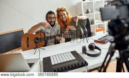 Man And Woman Pointing Down, Asking For Subscription While Recording Video Blog Or Vlog. Couple Of M