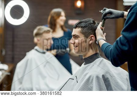 Side View Of A Young Cheerful Handsome Guy Visiting Barbershop Or Hair Salon, Professional Barber Ma