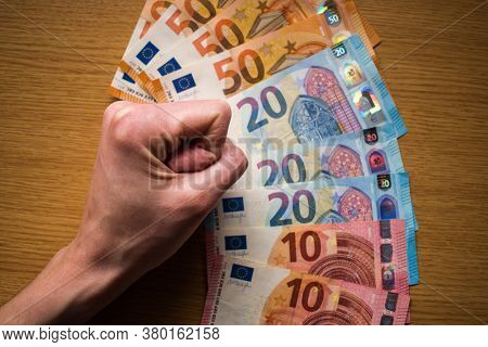 Woman Tight Fist And Paper Money Banknotes On Wooden Background