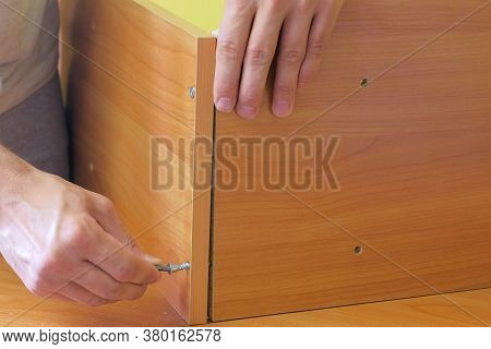 Man Is Collecting Parts Of Computer Table Screwing Shelf Screwdriver, Hands Closeup. Repairman Is As