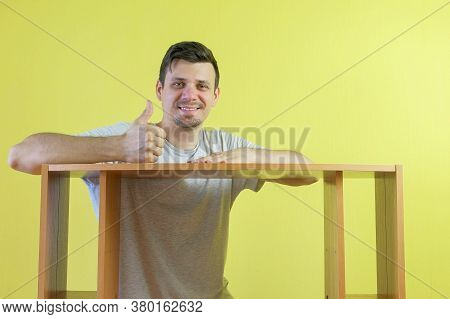 Portrait Of Smiling Man Master Repairman With Collected Table Looking At Camera On Yellow Wall Backg