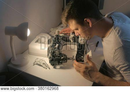 Repairman Master Is Testing Disassembles Sewing Machine In Workshop Repairing It Sitting At Table, S