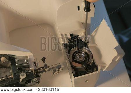 Seamstress Woman Is Repairing Mechanism Of Sewing Machine In Workshop, Closeup Hands View. Maintenan