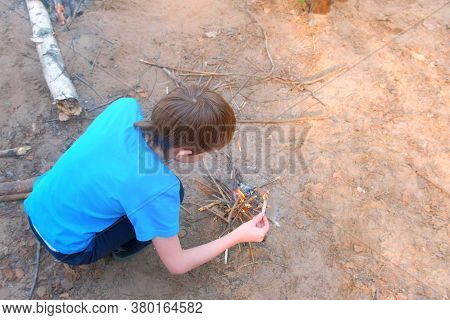 Child Boy In Blue T-shirt Is Making Bonfire From Firewoods Branches Nature Sitting Near It In Forest