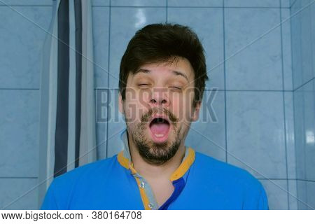 Sleepy Tired Young Man Is Yawning At Morning In Bathroom Looking At Camera. He Is Looking At Camera