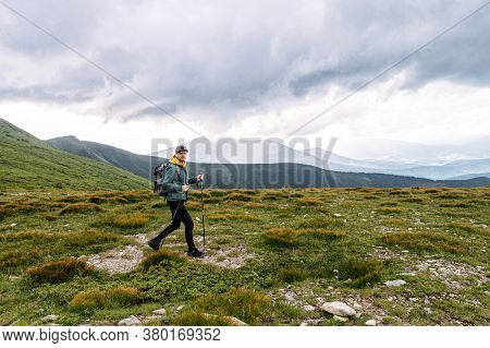 A Hipster Guy With Backpack Walks With A Poles For Nordic Walking On A Picturesque Hill. Active Leis