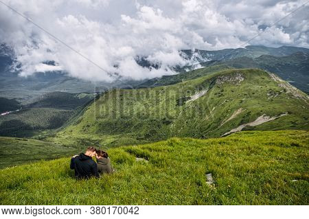 Man And Woman Sitting And Hugging On The Top Of The Mountain. Couple In Love Hikes Together, Spends