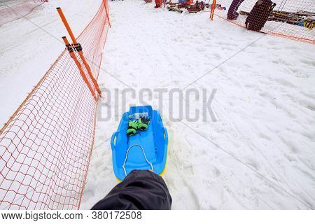 Blue Snow Sled In Small Snow Slope Zone For Kids Play,hand Holding The Sled On The Way Up To The Pea