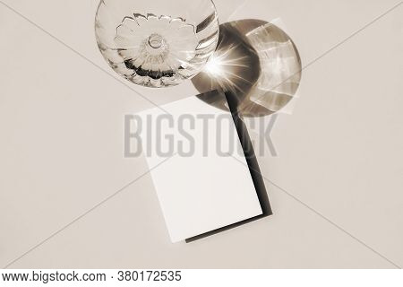 Summer Stationery Still Life Scene. Glass Of Water In Sunlight With Long Harsh Shadows On Beige Tabl