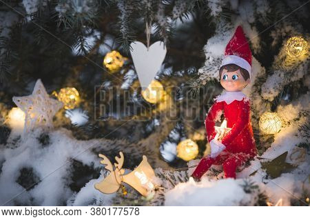 Cute Christmas Toy Sits In The Night On A Christmas Tree Covered With A Thick Layer Of Snow. Elf Is