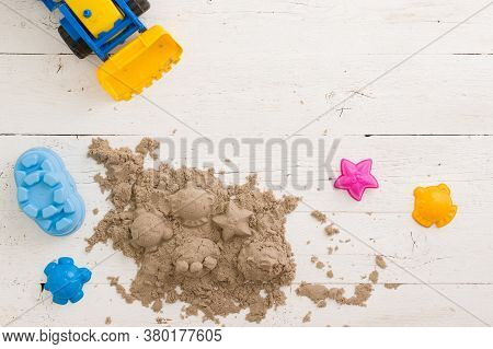 Top View On Colorful Molds For Sand And Kinetic Sand On A White Table Background. The Concept Of Dev