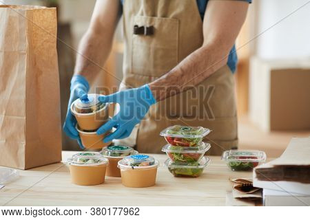 Closeup Of Unrecognizable Worker Wearing Protective Gloves Packaging Orders At Wooden Table In Food