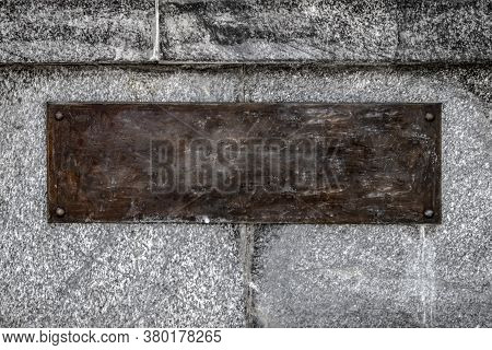 An Empty Brown Rusty Steel Plate Bolted With Four Round Bolts To A Gray Granite Wall. Template For D