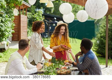 Multi-ethnic Group Of People Enjoying Dinner At Outdoor Terrace In Summer, Focus On Smiling Young Wo