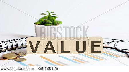 Value Word On Wood Blocks Concept With Chart, Coins, Notebook And Glasses.business Concept