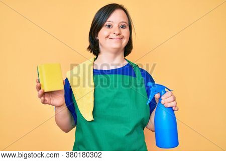 Brunette woman with down syndrome wearing apron holding scourer smiling with a happy and cool smile on face. showing teeth.