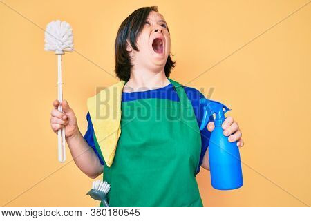 Brunette woman with down syndrome wearing apron holding scourer and toilet brush angry and mad screaming frustrated and furious, shouting with anger. rage and aggressive concept.