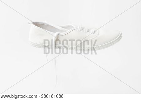 White Canvas Laced Unisex Plimsoll Shoe On Same Color Background With Copy Space. Classic Casual Spo