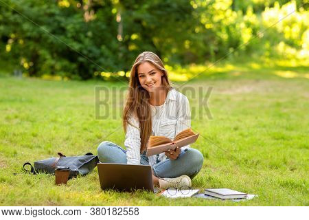 Preparing For Exams Outdoors. Smiling Student Girl Studying With Book And Laptop In Park, Doing Home