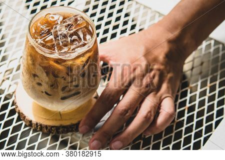Selective Focus Man Hold Cup Of Iced Coffee. Glass Of Cold Coffee With Milk On Table For Summertime,