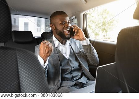 Delighted African Entrepreneur Having Pleasant Conversation On Phone, Using Laptop While Going To Of