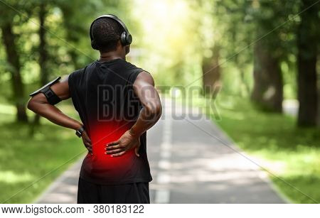 Back View Of Black Sportsman Touching Sore Zone On His Back, Having Back Pain During Jogging By Park