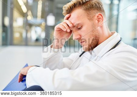 Young doctor sits exhausted in the hospital as a sign of overtime or overwork