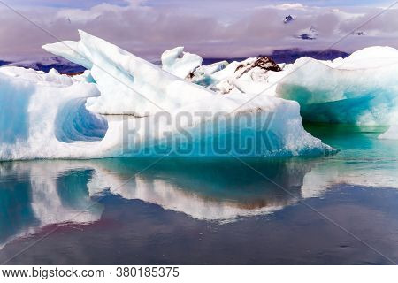 Iceland. The largest glacial lagoon Jokulsaurloun. The ice is covered in black and braun volcanic ash in some places. Cold early summer morning. The concept of northern and photo tourism