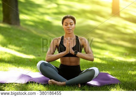 Yoga Practice Open Air. Peaceful African Girl In Sport Clothes Meditating At Park, Empty Space