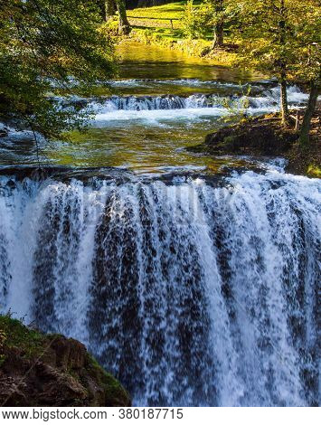Magnificent cascade of waterfalls on the Korana River. The forest surround the river. The small Croatian town of Slunj. The concept of ecological, active and photo tourism