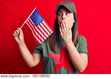 Beautiful woman wearing t-shirt with red star communist symbol holding united states flag covering mouth with hand, shocked and afraid for mistake. Surprised expression