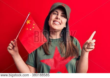 Beautiful patriotic woman wearing t-shirt with red star communist symbol holding china flag smiling happy pointing with hand and finger to the side